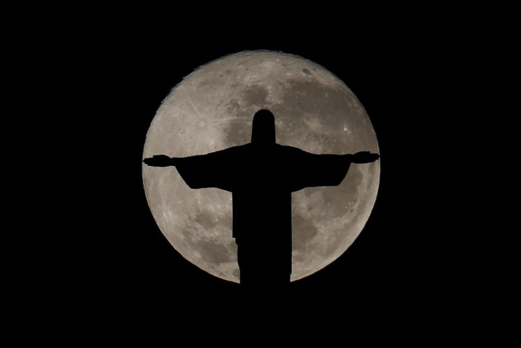 The full moon is pictured behind the Christ the Redeemer statue ahead of the 2016 Rio Olympic games in Rio de Janeiro, Brazil, July 19, 2016. REUTERS/Bruno Kelly